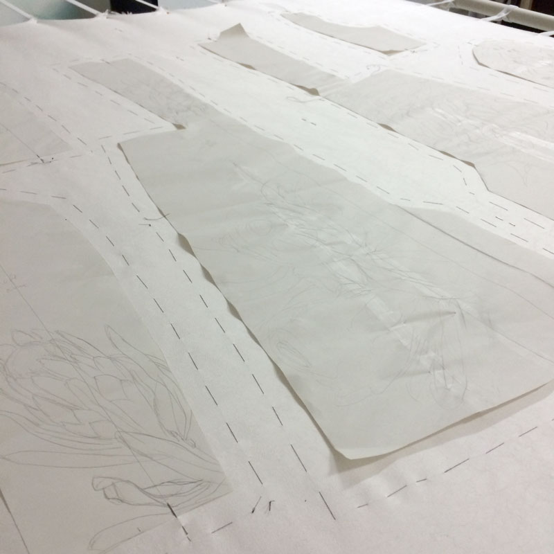 The sewing pattern pieces are laid out on the silk and an outline is tacked around the pattern pieces.